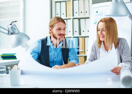 Pretty businesswoman and her colleague looking at blueprint at meeting - Stock Photo