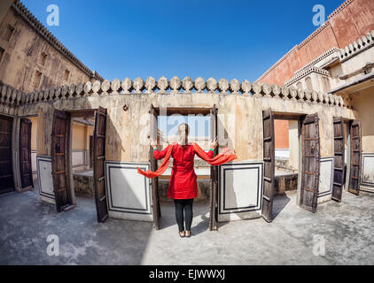 Woman in red dress with scarf opening the door in Hawa Mahal, Rajasthan, India - Stock Photo