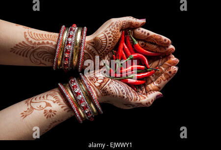 Woman hands with henna holding red chili isolated on black background with clipping path - Stock Photo