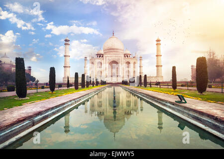 Taj Mahal tomb with reflection in the water at blue dramatic sky in Agra, Uttar Pradesh, India - Stock Photo