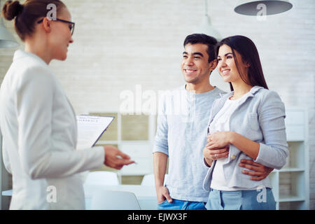 Young couple listening to female agent in realtor office - Stock Photo