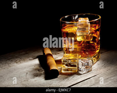 Glass of aged whiskey with cigar and ice cubes on wooden table - Stock Photo