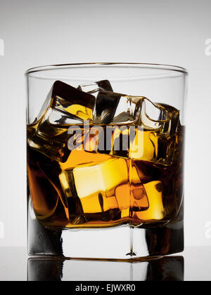 Aged noble glass of whiskey with ice - Stock Photo