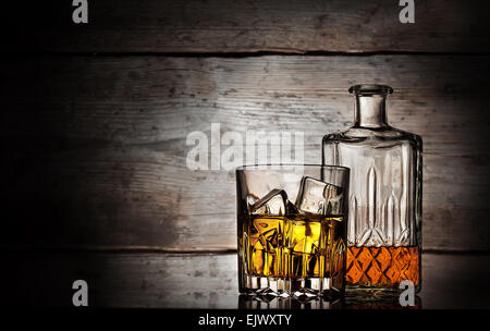 Glass of whiskey with ice cubes and faceted bottle on a wooden background - Stock Photo