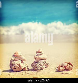 Vintage retro style image of coral pyramids on beach, Zen spa concept background. - Stock Photo