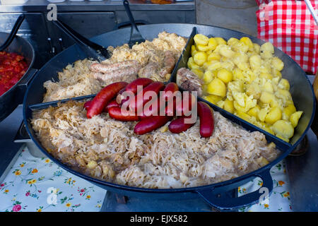 Street fast food. Stewed cabbage and smoked pork sausages in a big pig-iron frying pan - Stock Photo