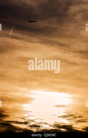 Silhouette of an aircraft taking off and a higher flying aircraft with sunset below and cloud detail in the sky - Stock Photo