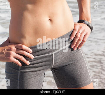 Woman in Sportswear with Hands on Hips, Mid Section, Close-up View - Stock Photo