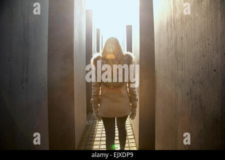 Back View of Young Woman Walking along the Concrete Steles of the Holocaust Memorial, Berlin, Germany - Stock Photo