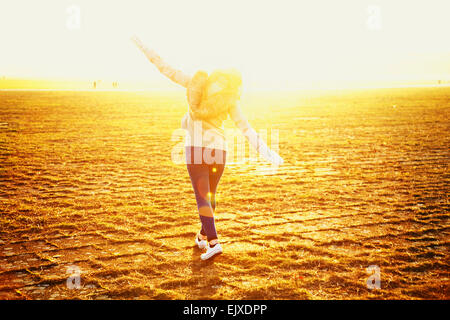 Back View of Young Woman Walking with Arms Outstretched - Stock Photo