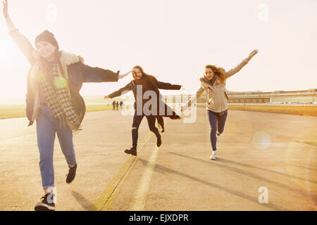 Teenage Girls Running with Arms Outstretched - Stock Photo