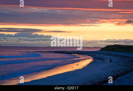 sunset at baleshare north uist  with lone fisherman - Stock Photo