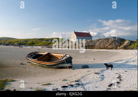 near Barra Eoligarry Airport a cottage idyllic with moored boat - Stock Photo