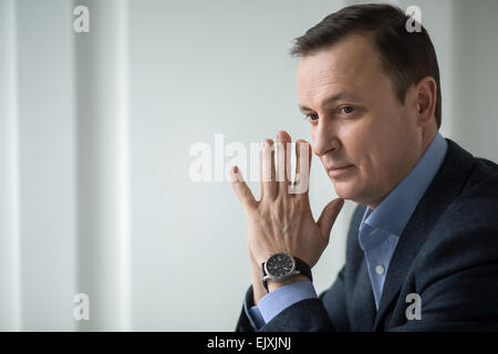 Attractive business man sitting pensively looking out the window - Stock Photo