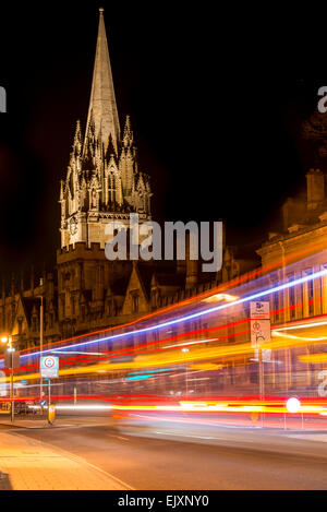 The University Church of St Mary, Oxford, UK from the High Street as traffic passing by leaves light trails - Stock Photo
