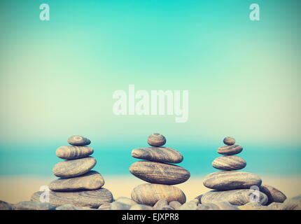 Vintage retro style image of stone pyramids on beach, Zen spa concept background. - Stock Photo