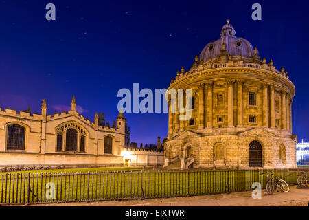 The Radcliffe Camera is a reading room of the Bodleian Library, Oxford University. Seen here at night with All Souls - Stock Photo