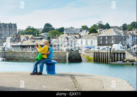 A couple in their thirties taking a selfie at Padstow, Cornwall. - Stock Photo