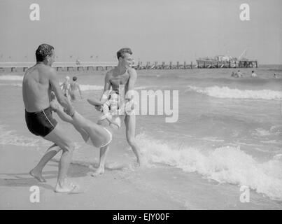 Two men throwing a young woman into the sea on Bournemouth beach. 10th Aust 1952
