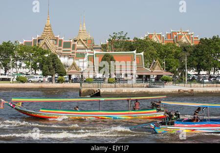 Longtail river taxi boats passing the Royal Palace on Chao Phraya River in Bangkok Thailand - Stock Photo