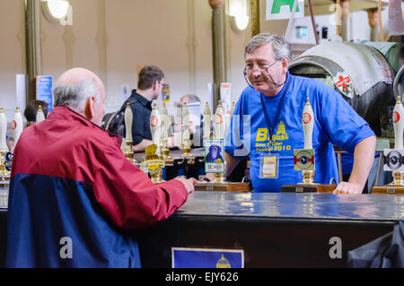 A barman serves customers at a CAMRA real ale festival. - Stock Photo