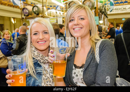Two young ladies enjoying their pints at a CAMRA real ale festival. - Stock Photo