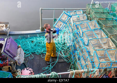 Neil McCulloch, prawn fisherman, loading his fishing boat with nets before leaving to go fishing in the Firth of - Stock Photo