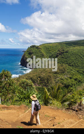 Hiker ventures on trail into Pololu Valley on the Big Island of Hawaii