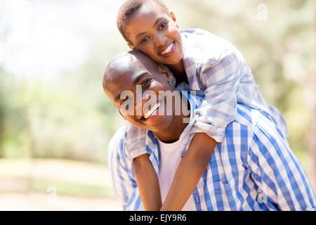 pretty African woman enjoying piggyback ride on boyfriend outdoors - Stock Photo