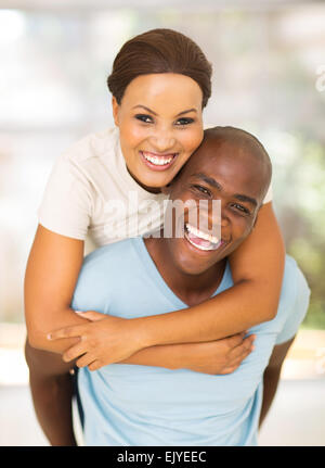 cheerful young African American couple having fun with piggyback - Stock Photo