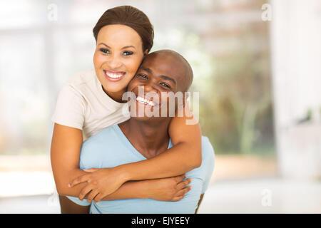 happy African woman enjoying piggyback ride on boyfriend - Stock Photo