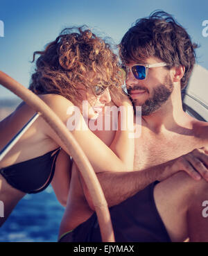 Portrait of a cute happy couple sitting on sailboat and enjoying bright summer day, enjoying romantic honeymoon - Stock Photo