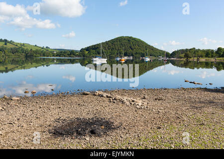 Beautiful lake on calm idyllic summer morning with BBQ barbecue ashes from night before - Stock Photo