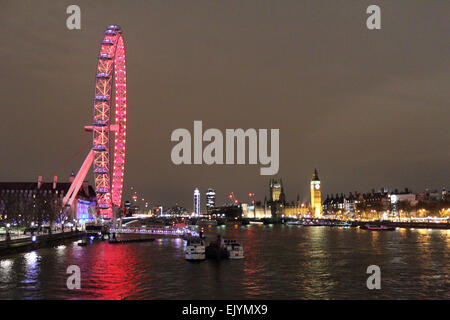 London England UK. 2nd April 2015. After dark on the Southbank the London Eye is lit up with the red lights of the - Stock Photo