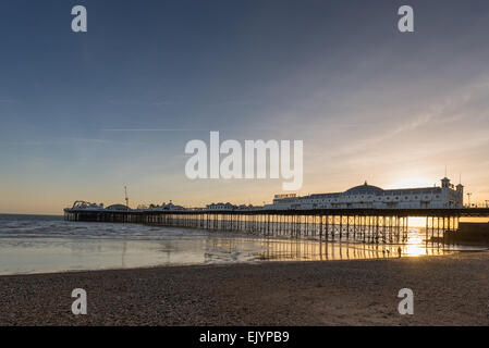 Brighton Pier at low tide during sunset - Stock Photo
