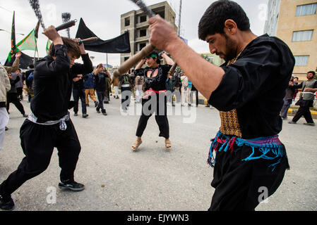 Shia Muslims flagellate themselves during street procession in the Day of Ashura, tenth day of Muharram and commemoration - Stock Photo
