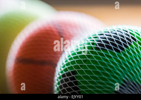 Row of differing toy balls lined up & bound in a net. - Stock Photo