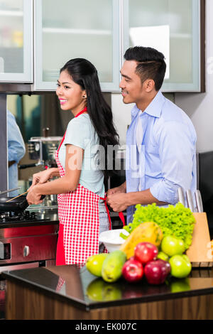 Couple in domestic Kitchen cooking food - Stock Photo