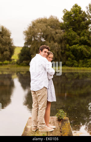 romantic young couple standing on river pier - Stock Photo