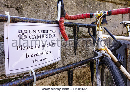 Bike locked to a railing in Cambridge next to a sign asking people to not leave bicycles here, thank you - Stock Photo