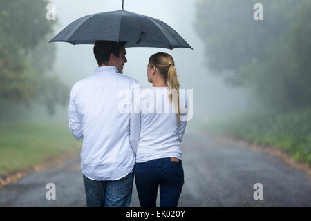 rear view of romantic couple walking in rain - Stock Photo
