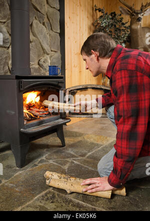 mid-adult man adding logs to a wood burning stove fire in rustic setting - Stock Photo