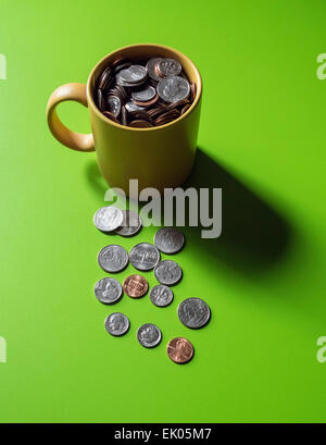 Small change, a concept. A coffee mug filled with US coins - Stock Photo