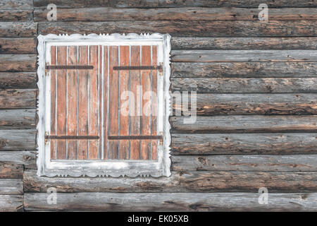 Closed shutters on a wooden chalet worn by the snow - Stock Photo