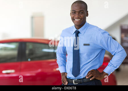 African American vehicle sales consultant inside showroom - Stock Photo
