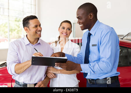 happy middle aged couple buying a new car at vehicle showroom - Stock Photo