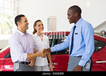 happy car salesman handshaking with middle aged buyer - Stock Photo