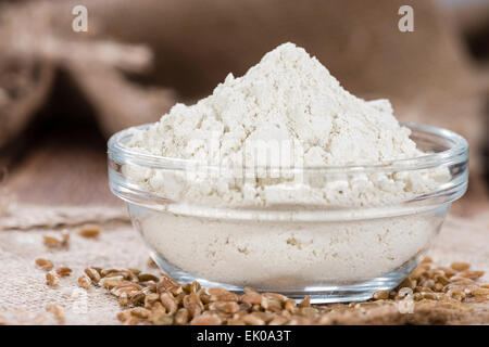 Portion of Spelt Flour (close-up shot) on rustic wooden background - Stock Photo
