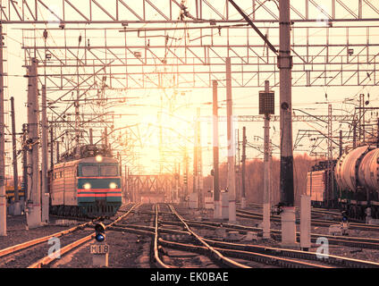 Two long freight trains moves through the station at sunset. - Stock Photo