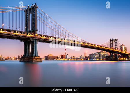 Manhattan Bridge illuminated at dusk (very long exposure for a perfectly smooth water) - Stock Photo